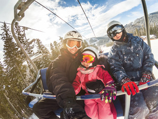 happy smiling family skiers on ski lift making selfie