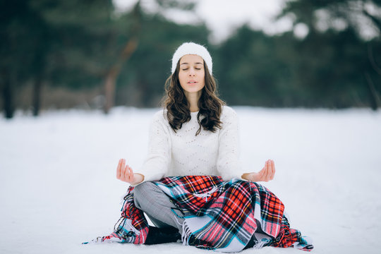 Young woman is meditating in the yoga pose on the snow during the winter walk.