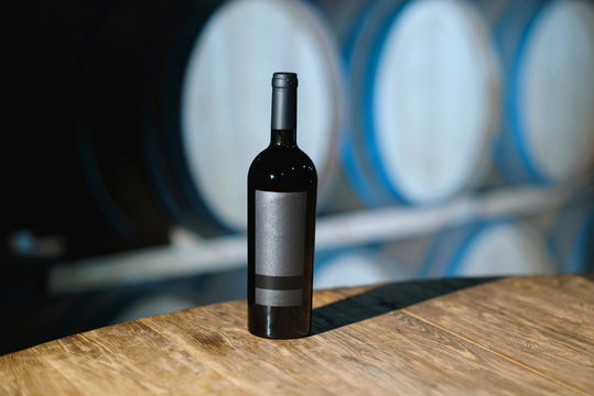 bottle with red wine on wooden table
