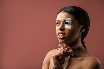 angry naked african american woman with white paint stroke on eye holding bow tie and looking away isolated on brown