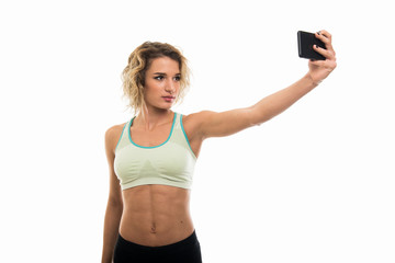 Portrait of beautiful young fit girl making selfie