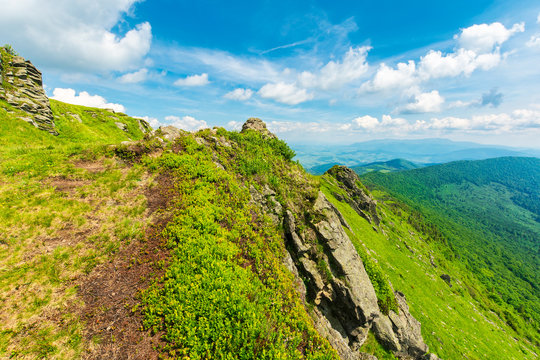 rocky edge of a grassy hillside. mountain ridge in the distance. wonderful summer weather. fleecy clouds on the blue sky