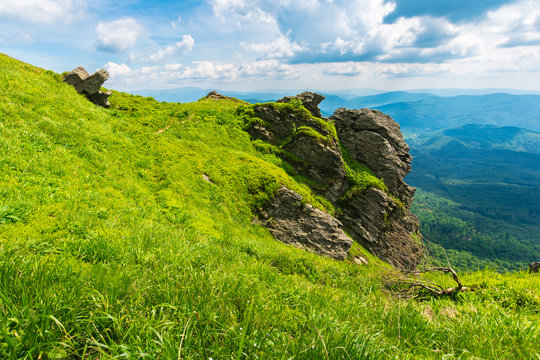 rocky formation on a grassy hillside. path among the grass to the boulders. beautiful mountain ridge in the distance. wonderful summer weather. fluffy clouds on the blue sky