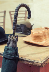 Old umbrella and hats on a vintage table. Red Vintage style wooden table and chairs.