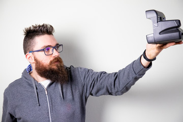 Caucasian bearded man taking a selfie photo with vintage polaroid camera
