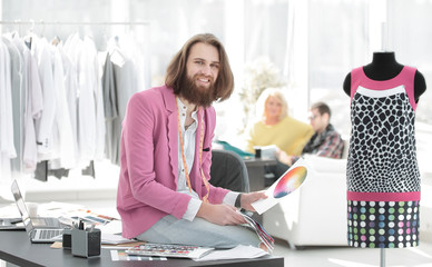 portrait of a clothing designer sitting on a Desk in the Studio