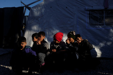 Children sit outside a tent at a makeshift camp next to the Moria camp for refugees and migrants on the island of Lesbos