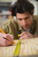 Male carpenter measuring and marking wood