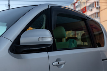 Side rear-view mirror on the body of a minivan of gray color with elements of chromed iron in the design and headlight turn.