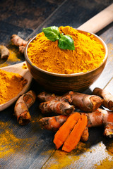 In de dag Kruiden Composition with bowl of turmeric powder on wooden table
