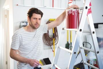 Male painter standing near ladder in workshop