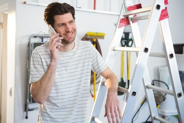 Male painter talking on mobile phone