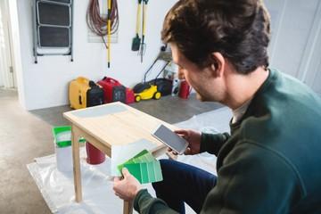Male carpenter checking color shade