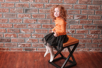 cute little girl sitting on a chair in a new living room.