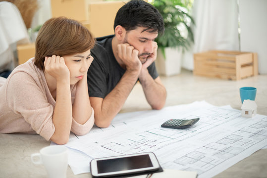 Stressed Young couple calculating their budget.