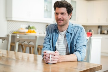 Man having coffee in kitchen at home