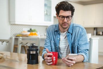 Man using mobile phone while having coffee in kitchen