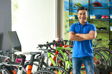 Confident smiling bicycle store shop assistant looking at camera