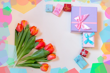 Tulip flowers and colorful gift boxes on pastel background. Top view with copy space.