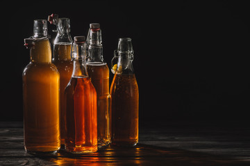 homemade organic tea in glass bottles isolated on black