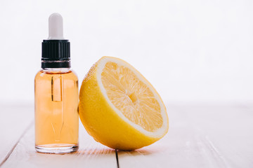 cbd oil in bottle with dropper and half of lemon on wooden surface isolated on white
