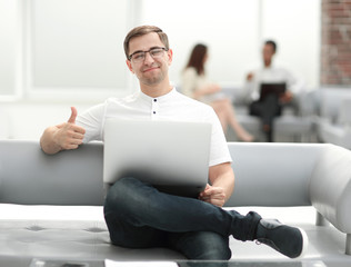 smiling man with laptop showing thumb up
