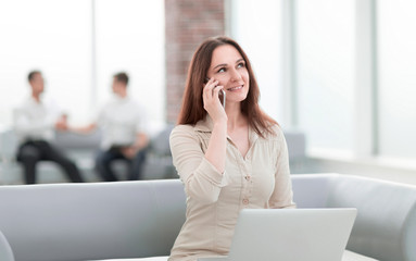 young business woman communicates with her partners using laptop and smartphone