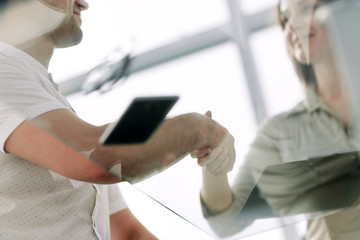 bottom view.businessman and businesswoman shaking hands over the Desk