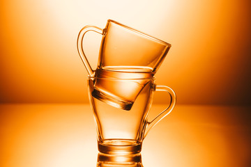 selective focus of two cups of water on orange background