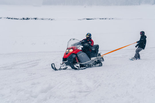 Man snowboarding holding a rope towed behind a snowmobile on the frozen lake between beautiful snowy forest. Extreme sport
