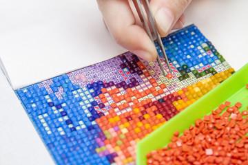 Girl collect diamond painting. Diamond embroidery with a tweezers. Acrylic rhinestones. Closeup, selective focus