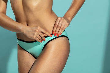 Hands with red nails on bikini
