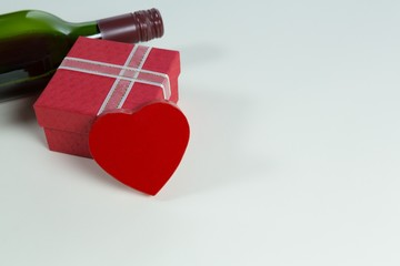 Wine bottle with valentine gift and decoration on white