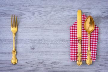 Gabel, Messer und Löffel mit einer Serviette am Holztisch