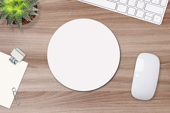 Mouse pad mockup. Round white mat on the table with props, mouse and keyboard