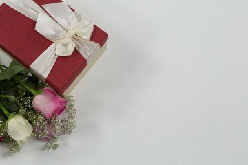 Flower bouquet and gift on white background