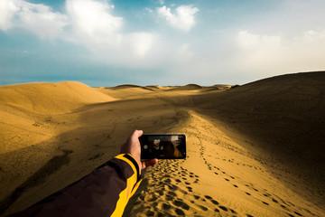 Caucasian hand with modern technologyh phone taking picture if sand yellow desert with blue sky in background - scenic beautiful landscape for alternative discover world adventure vacation