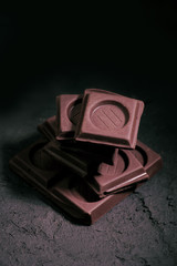 pile of dark chocolate pieces on rustic black textured background
