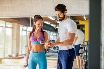 Picture of strong smiling personal fitness trainer helping his cute female client with heavy weights workout in gym.