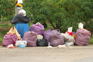 Pile of many garbage bags on nature scene