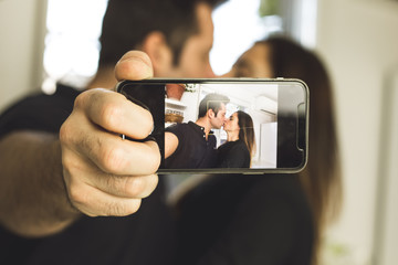 Couple making a selfi kissing and smiling. Love and romance between man and woman