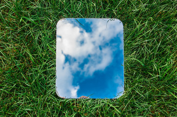 Wall Mural - Rectangular mirror reflecting the blue sky with clouds lying on the green grass