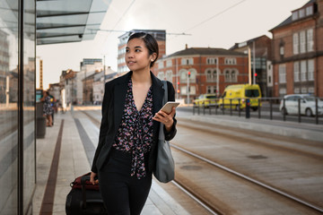 Asian businesswoman waiting with her luggage at a tram stop