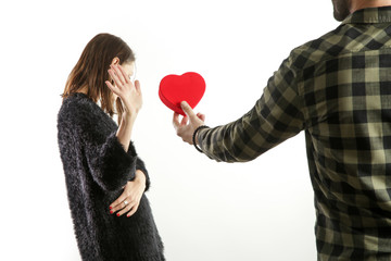 Portrait of a young couple having conflict. Man asking for forgiveness offering a red heart-shaped gift to his depressed girlfriend