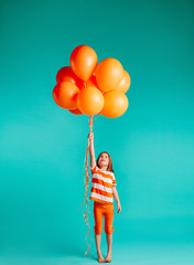 Cute girl holding orange balloons