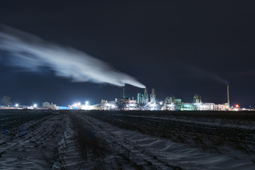 A night view of an industrial unit, a wood-processing plant with fuming pipes and a high-illuminated area on the background of a snow-covered field and a bicycle with a red light.