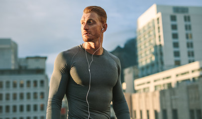 Portrait of a fitness man standing on rooftop listening to music