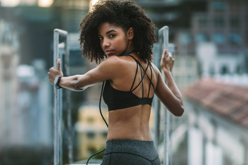 Rear view of a fitness woman standing on rooftop and looking bac