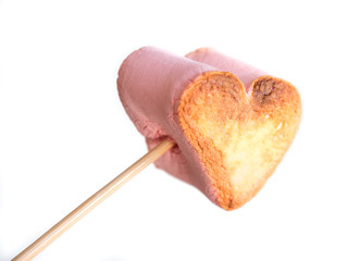 roasted heart form marshmallows on a skewer in female hand on white background