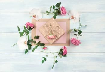 Floral frame consists of roses and orchids flowers and gift box on wooden background